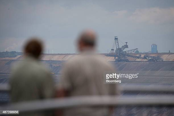 Sightseers stand on a viewing platform as a giant excavator operates at an open pit lignite mine also known as brown coal operated by RWE AG in...