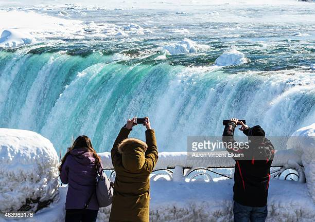 Sightseers take pictures of a nearly frozen Niagara Falls on February 20 2015 in Niagara Falls Ontario Canada Much of the United States and Canada...