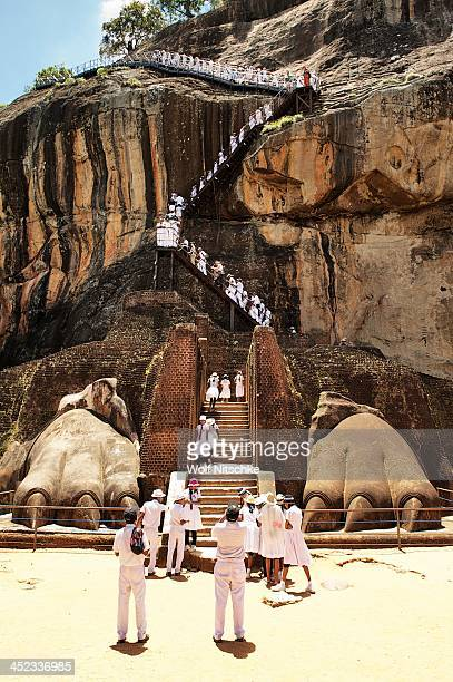 Students and school children dressed in white climb the steps between of the lion rock palace The paws are all that are left of the previously...