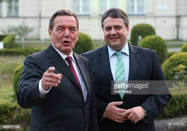 Sigmar Gabriel German Economoy Minister and Chairman of the German Social Democrats greets former German Chancellor Gerhard Schroeder at a reception...