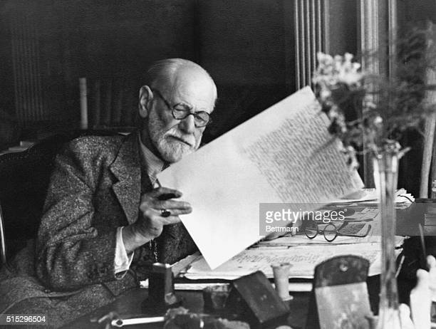 Sigmund Freud 18561939 Austrian psychiatrist in the office of his Vienna home looking at a manuscript