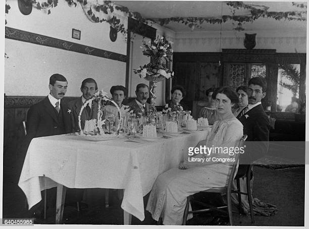 Sigmund Freud fourth from left sits at an elegant dining table with the rest of his family including his daughter Anna far right