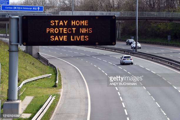 A sign above the M8 motorway in Glasgow on April 16 2020 advises people to stay home as Britain continues to enforce a nationwide lockdown in an...