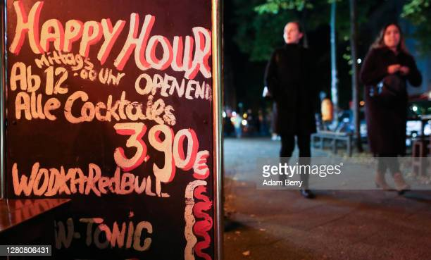 Sign advertises all-day Happy Hour cocktails for sale at a bar prior to its closing at 11pm on October 17, 2020 in Berlin, Germany. About 11 bars and...