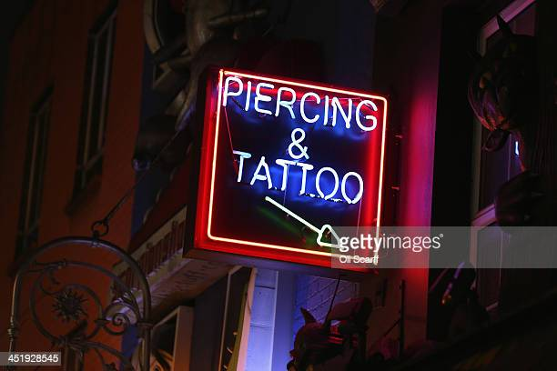 A sign advertises tattooing and piercing near Camden Market on November 25 2013 in London England The proposed route of the HS2 high speed rail link...
