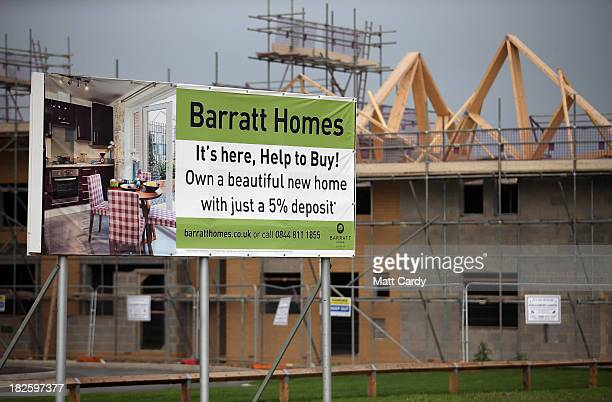 A sign advertises the Help to Buy scheme as construction workers build new houses on a housing development in Filton on October 1 2013 in Bristol...