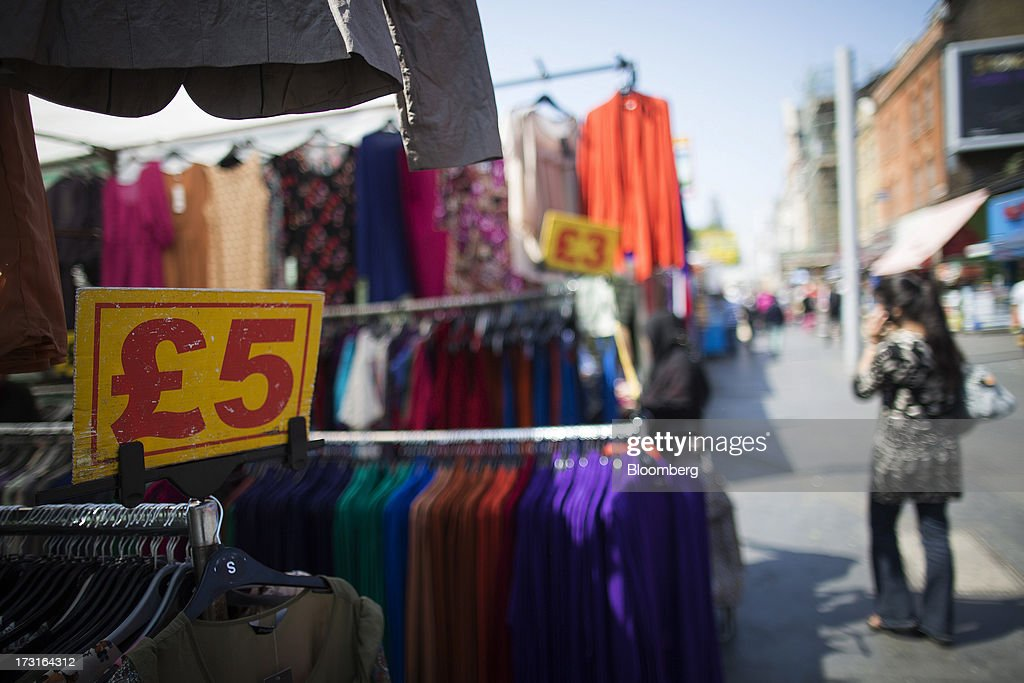 A sign advertises the price in pounds on a clothes stall at an outdoor market in London, U.K., on Monday, July 8, 2013. Britain's economy could be in line for a period of 'strong catch-up growth' once it gets through the current weakness, according to Capital Economics Ltd. Photographer: Simon Dawson/Bloomberg via Getty Images