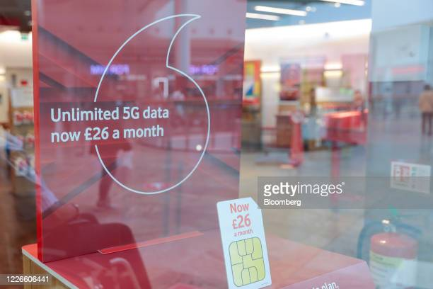 A sign advertising 5G data plans is displayed in the window of a Vodafone Group Plc mobile phone store in Reading UK on Monday July 13 2020 UK Prime...