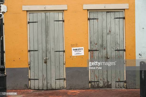 A sign advertising a bar between two locked doors in the French Quarter of New Orleans amid restrictions in place to help deal with the Covid19...