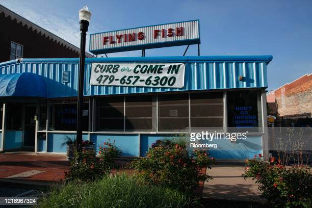 Sign advertising curbside pickup outside Flying Fish restaurant in Bentonville, Arkansas, U.S., on Thursday, May 28, 2020. The annual Walmart Inc....
