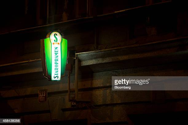 A sign advertising Staropramen beer manufactured by Pivovary Staropramen AS brewery a unit of Molson Coors Brewing Co sits illuminated outside a bar...
