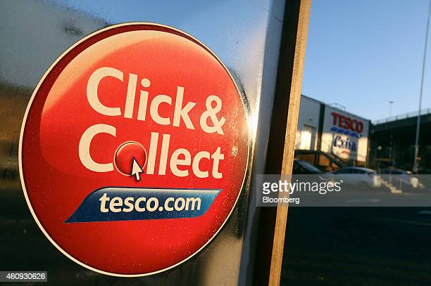 A sign advertising Tesco Plc's clickandcollect internet shopping services sits on a cart shelter outside one of the company's supermarket stores in...