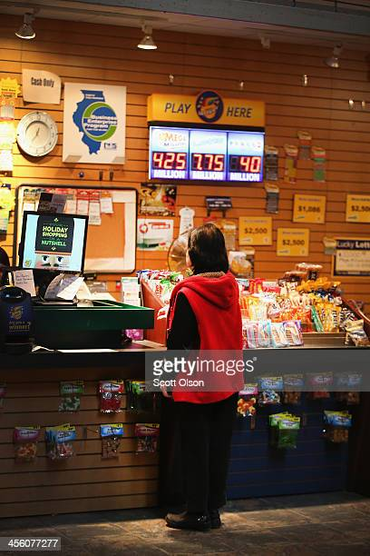 A sign advertising the Mega Millions lottery jackpot hangs in Debbie's Newstand on December 13 2013 in Chicago Illinois Tonight's Mega Millions...