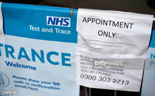 A sign advises members of the public that COVID19 testing is by appointment only and suggests they should book a hometesting kit instead on a barrier...