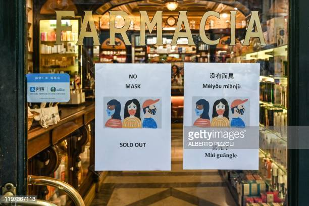 Sign advising clients in various languages, including Chinese, that respiratory masks are sold out, is displayed on January 29, 2020 at a pharmacy in...