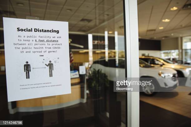 Sign advising customers to practice social distancing is displayed on the door of a General Motors Co. Buick and GMC car dealership in Woodbridge,...