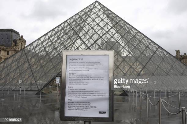 A sign advising of the closure of the Louvre Museum due to staff worries over the coronavirus outbreak sits on display outside the tourist attraction...