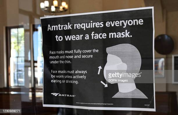 Sign advising passengers of a face mask requirement is seen on a window at the Orlando Amtrak station on the first day that the Transportation...