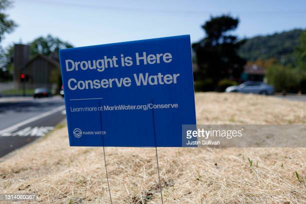 Sign advocating water conservation is posted in a field of dry grass on April 23, 2021 in San Anselmo, California. As the worsening drought takes...