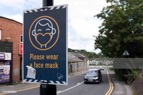 Sign affixed to a lamp post reminds people to wear a face mask to prevent the spread of Covid-19 with an oncoming car in the background on 10th...