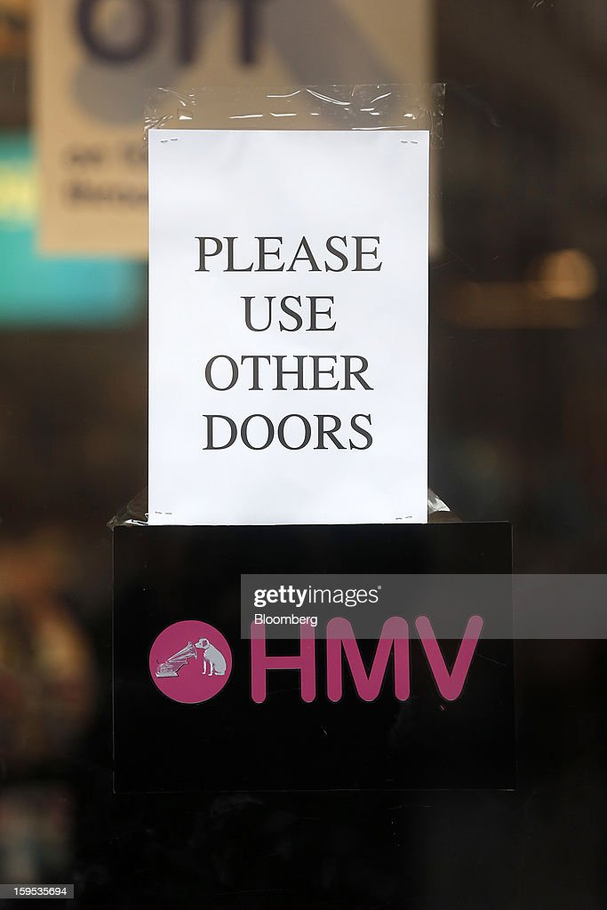 A sign alerts customers to use another door outside an HMV store in London, U.K., on Tuesday, Jan. 15, 2013. Endless LLP, a private-equity firm that focuses on companies in distress, contacted HMV Group Plc's prospective administrators with a view to buying the U.K.'s biggest retailer of CDs and DVDs. Photographer: Simon Dawson/Bloomberg via Getty Imagesn
