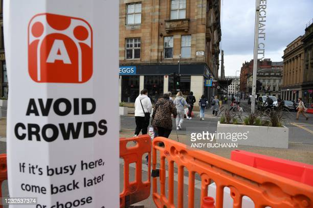 """Sign alerts pedestrians and shoppers to """"Avoid Crowds"""" due to Covid-19 in Glasgow on April 26, 2021 following the relaxing of some Covid-19..."""