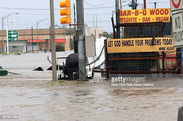 """Sign amidst the flooded streets of Port Arthur, Tex., reads """"Let God Handle Your Problems Today - Mine Also!"""" The town, which is located on the..."""