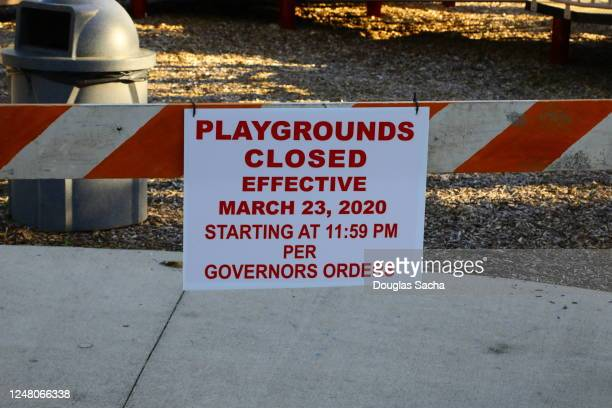 sign and barricade at the entrance of a playground warning of covid-19 pandemic closure - governor stock pictures, royalty-free photos & images