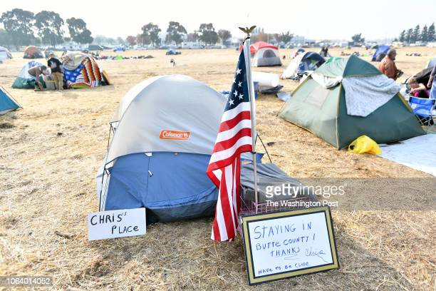 A sign and flag mark a temporary home at an evacuee encampment at a Walmart parking lot in Chico California on November 19 2018