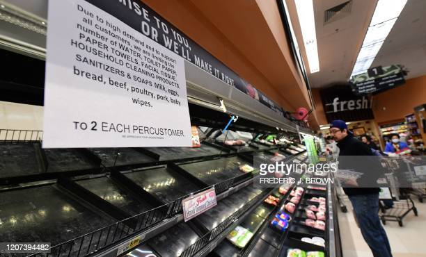 A sign announces a twoitem limit for certain items as people shop for food at a Ralph's Supermarket in Monterey Park California on March 16 2020 as...