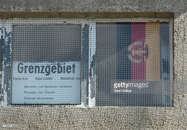 A sign announcing Border Area and a former East German flag are visible in the window of a former guard tower that once stood at the former Berlin...