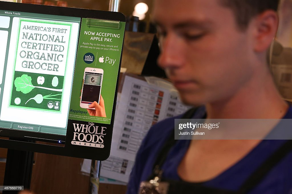 A sign announcing that Whole Foods is accepting Apple Pay is posted on a cash register at a Whole Foods store on October 20, 2014 in San Francisco, California. Apple's Apple Pay mobile payment system launched today at select banks and retail outlets.