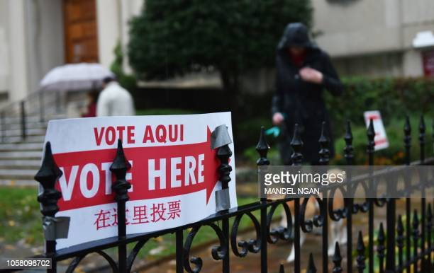 A sign announcing the location of a polling station is seen outside a church in Washington DC on November 6 2018 Americans started voting Tuesday in...