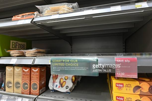 Sign apologising for a limited choice of products is displayed in a supermarket at Nine Elms, south London on July 22, 2021. - British supermarkets...