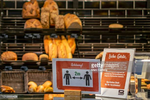 A sign asks customers to keep distance to other people whilst waiting in the queue at the bakery on March 19 2020 in Hamburg Germany Everyday life in...
