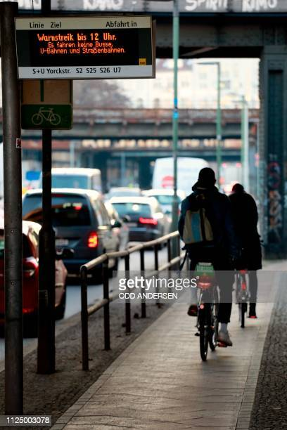 A sign at a bus stop warns of a strike as commuters on bicycles make their way as traffic builds up along Yorckstrasse in Berlin on February 15 2019...