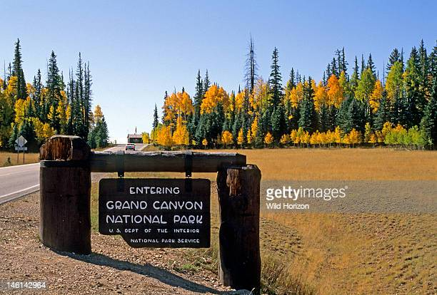 Sign at the entrance to Grand Canyon National Park in a subalpine meadow in autumn behind is a sprucefir forest with quaking aspens Populus...