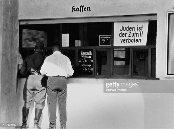 Sign at the ticket office of a public swimming pool, reading, 'Juden ist der Zutrit verboten' , Nazi Germany, circa 1938.