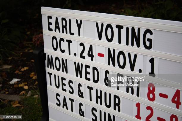 sign at town voting precinct with voting hours & dates - polling station stock pictures, royalty-free photos & images
