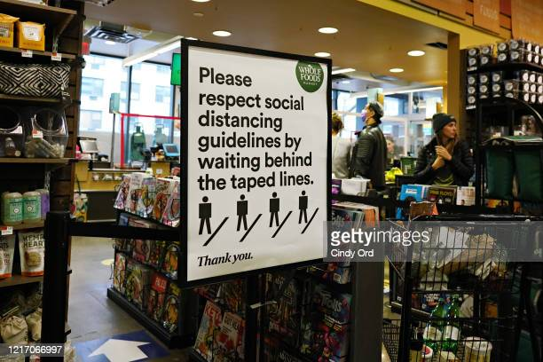 """Sign at Whole Foods reads, """"Please respect social distancing guidelines by waiting behind the taped lines"""" amid the coronavirus pandemic on April 05,..."""