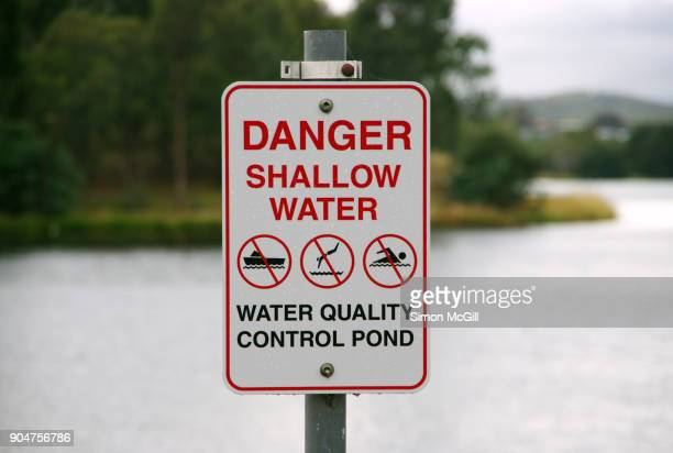 danger: shallow water - water quality control pond sign at yerrabi pond, australian capital territory, australia - australian capital territory stockfoto's en -beelden