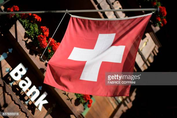 A sign 'Bank' is seen beneath a Swiss flag on the front of a local banking branch on August 22 2017 in Gstaad / AFP PHOTO / Fabrice COFFRINI