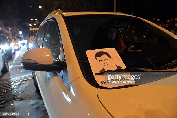 A sign bearing a portrait ofUkrainian President Viktor Yanukovych and reading 'traitor' is pictured on windshield of a car during a rally on...