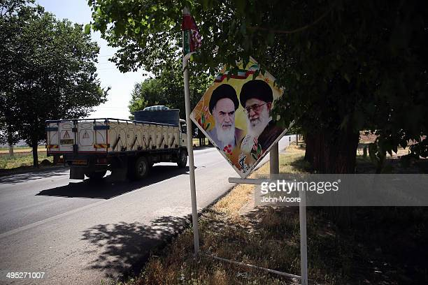 A sign bearing portraits of the Ayatollah Khomeini and Iran's current supreme leader Ayatollah Khamenei stands near the tomb of Cyrus the Great on...