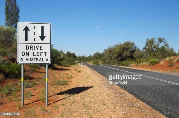 drive on left in australia sign beside lasseter highway, northern territory, australia - 左利き ストックフォトと画像
