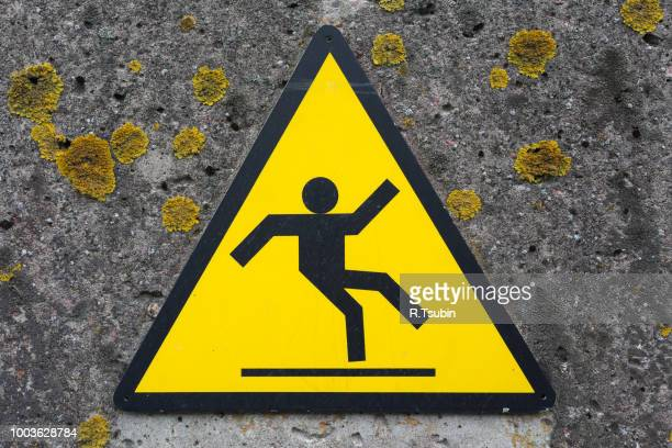 sign beware slippy on concrete wall - danger stock photos and pictures