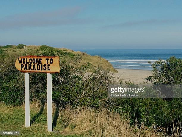Sign Board By Trees Against Sea And Blue Sky
