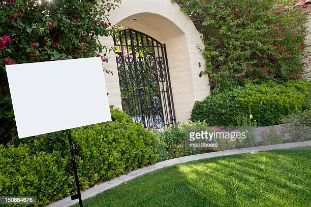 Sign board on lawn with house in background