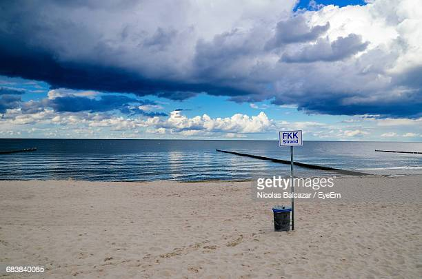 Sign Board On Sand At Beach Against Cloudy Sky