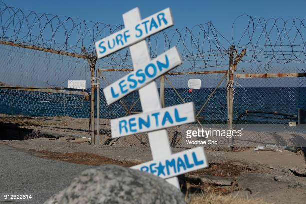Sign boards of a closed surf shop is seen in front of barbed wire along the beach in Yangyang Ganwon province in South Korea on February 1 2018 The...